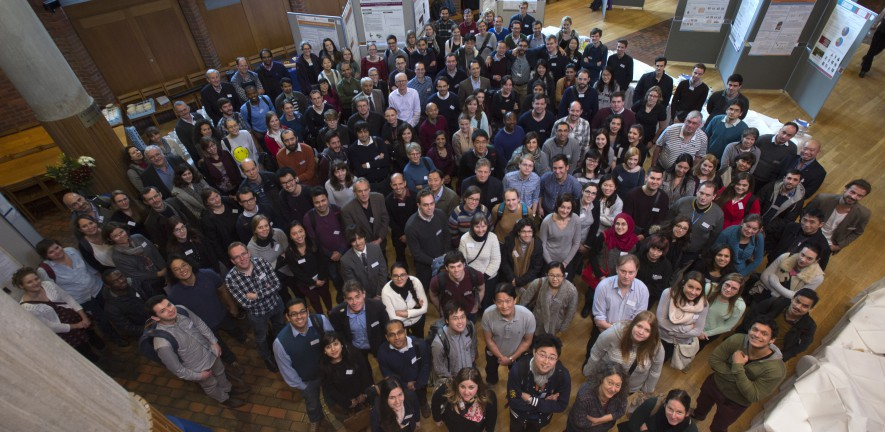 Group photo of the IMS staff, taken from a balcony looking down, with the staff looking up